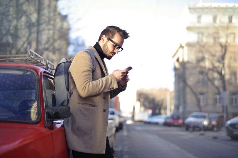 Man on the street looking at his smartphone