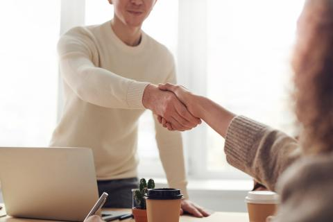 Tester and developer shaking hands across a table